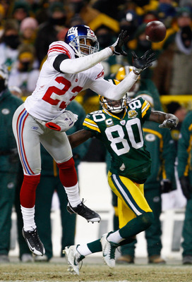 GREEN BAY, WI - JANUARY 20:  Cornerback Corey Webster #23 of the New York Giants intercepts a Brett Favre #4 of the Green Bay Packers pass in front of Donald Driver #80 of the Packers in overtime of the NFC championship game on January 20, 2008 at Lambeau