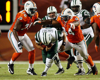 MIAMI - OCTOBER 12:  Quarterback Mark Sanchez #6 of the New York Jets is sacked by defensive end Randy Starks #94 of the Miami Dolphins at Land Shark Stadium on October 12, 2009 in Miami, Florida.  (Photo by Marc Serota/Getty Images)