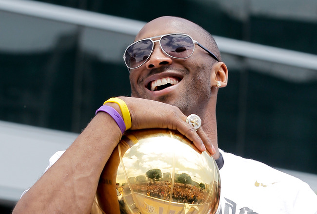 LOS ANGELES, CA - JUNE 21:  Los Angeles Lakers guard Kobe Bryant laughs with the championship trophy while riding in the victory parade for the the NBA basketball champion team on June 21, 2010 in Los Angeles, California. The Lakers beat the Boston Celtic