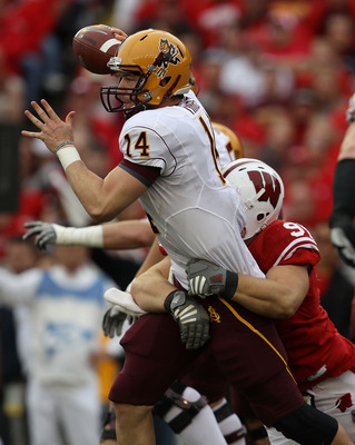 MADISON, WI - SEPTEMBER 18: Steven Threet #14 of the Arizona State Sun Devils tries to pass as  Patrick Butrym #95 of the Wisconsin Badgers drags him down at Camp Randall Stadium on September 18, 2010 in Madison, Wisconsin. Wisconsin defeated Arizona Stat