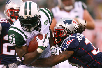 EAST RUTHERFORD, NJ - SEPTEMBER 19:  LaDainian Tomlinson #21 of the New York Jets is tackled by Brandon Meriweather #31 of the New England Patriots at the New Meadowlands Stadium on September 19, 2010 in East Rutherford, New Jersey. The Jets defeated the