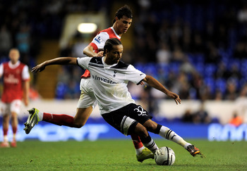 LONDON, ENGLAND - SEPTEMBER 21:  Benoit Assou-Ekotto of Spurs is challenged by Marouane Chamakh of Arsenal during the Carling Cup third round match between Tottenham Hotspur and Arsenal at White Hart Lane on September 21, 2010 in London, England.  (Photo
