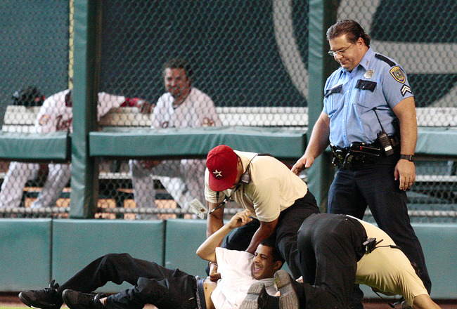 HOUSTON - MAY 31:  Stadium security and Houston Police tackle a fan who ran on the field in the eighth inning during a baseball game between the Washington Nationals and the Houston Astros from Minute Maid Park on May 31, 2010 in Houston, Texas.  (Photo b