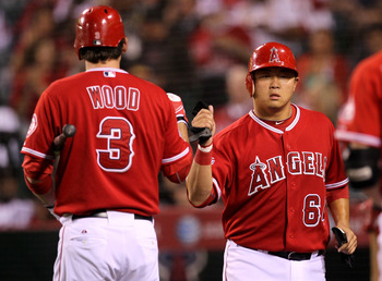 ANAHEIM, CA - SEPTEMBER 21:  Hank Conger #64 of the Los Angeles Angels of Anaheim is greeted by Brandon Wood #3 as he returns to the dugout after scoring a run in the second inning against the Texas Rangers on September 21, 2010 at Angel Stadium in Anahei