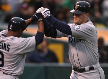 OAKLAND, CA - SEPTEMBER 08:  Russell Branyan #30 of the Seattle Mariners celebrates with Chone Figgins #9 after hitting a two run home against the Oakland Athletics in the first inning during a Major League Baseball game at the Oakland-Alameda County Coli