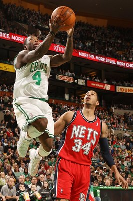 BOSTON - FEBRUARY 27:  Nate Robinson #4 of the Boston Celtics takes a shot as Devin Harris #34 of the New Jersey Nets defends at the TD Garden on February 27, 2010 in Boston, Massachusetts. The Nets defeated the Celtics 104-96.  NOTE TO USER: User express