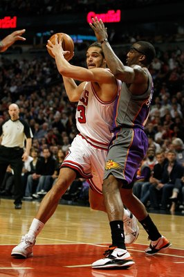 CHICAGO - MARCH 30: Joakim Noah #13 of the Chicago Bulls looks to pass under pressure from Amar'e Stoudemire #1 of the Phoenix Suns at the United Center on March 30, 2010 in Chicago, Illinois. The Suns defeated the Bulls 111-105. NOTE TO USER: User expres