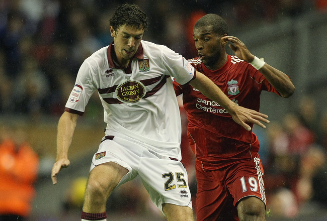 LIVERPOOL, ENGLAND - SEPTEMBER 22:  Ben Tozer of Northampton Town looks to play the ball under pressure from Ryan Babel of Liverpool during the Carling Cup Third Round match between Liverpool and Northampton Town at Anfield on September 22, 2010 in Liverp