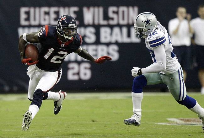 HOUSTON - AUGUST 28: Wide receiver Jacoby Jones #12 of the Houston Texans fends off Orlando Scandrick #32 in the first quarter at Reliant Stadium on August 28, 2010 in Houston, Texas. (Photo by Bob Levey/Getty Images)