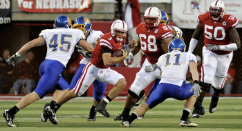 LINCOLN, NE - SEPTEMBER 25: !Quarterback Taylor Martinez #3 of the Nebraska Cornhuskers tries to elude linebacker Michael Lien #45 and linebacker Erich Feller #11of the South Dakota State Jackrabbits during first half action of their game at Memorial Stad