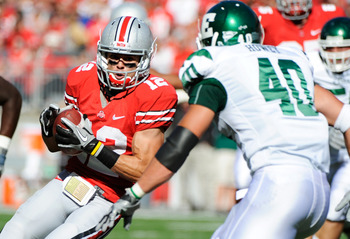 COLUMBUS, OH - SEPTEMBER 25:  Dane Sanzenbacher #12 of the Ohio State Buckeyes looks for running room after catching a pass as Neal Howey #40 of the Eastern Michigan Eagles defends at Ohio Stadium on September 25, 2010 in Columbus, Ohio. Sanzenbacher had