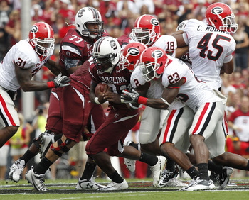 COLUMBIA, SC - SEPTEMBER 11: Tailback Marcus Lattimore #21 of the South Carolina Gamecocks (center with ball) is tackled by cornerback Brandon Boykin #2 and free safety Jakar Hamilton #23 of the Georgia Bulldogs during the game at Williams-Brice Stadium o