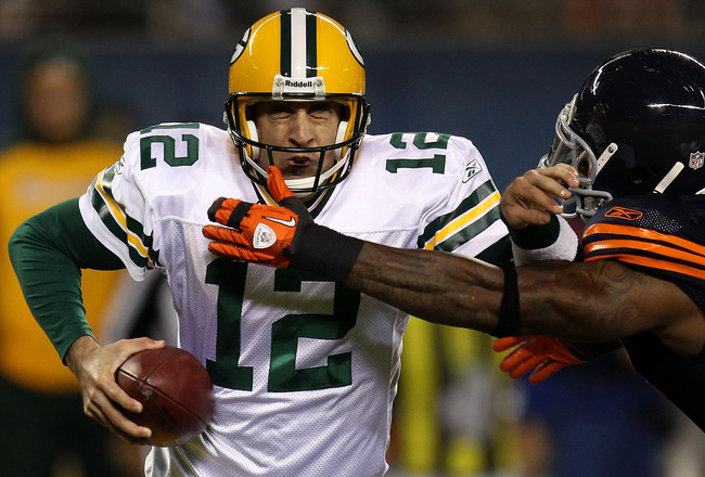 CHICAGO - SEPTEMBER 27:  Aaron Rodgers #12 of the Green Bay Packers attempts to escape pressure from Mark Anderson #97 of the Chicago Bears in the first half at Soldier Field on September 27, 2010 in Chicago, Illinois.  (Photo by Jonathan Daniel/Getty Ima
