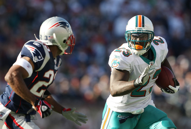 FOXBORO, MA - NOVEMBER 08:  Ronnie Brown #23 of the Miami Dolphins carries the ball as Leigh Bodden #23  of the New England Patriots defends on November 8, 2009 at Gillette Stadium in Foxboro, Massachusetts.  (Photo by Elsa/Getty Images)