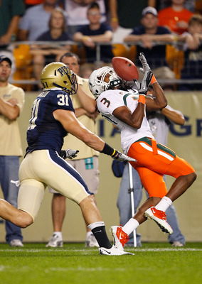 PITTSBURGH - SEPTEMBER 23:  Travis Benjamin #3 of the Miami Hurricanes catches a pass in front of Dom Decicco #31 of the Pittsburgh Panthers on September 23, 2010 at Heinz Field in Pittsburgh, Pennsylvania.  (Photo by Jared Wickerham/Getty Images)