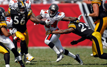 TAMPA, FL - SEPTEMBER 26:  Running back Carnell Williams #24 of the Tampa Bay Buccaneers runs through the tackle of safety Ryan Clark #25 of the Pittsburgh Steelers during the game at Raymond James Stadium on September 26, 2010 in Tampa, Florida. The unde