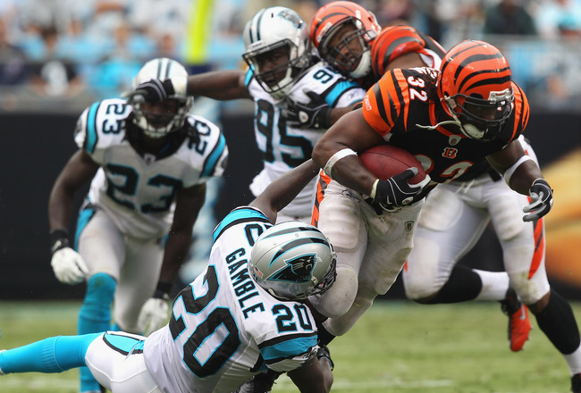 CHARLOTTE, NC - SEPTEMBER 26:  Cedric Benson #32 of the Cincinnati Bengals is tackled by Chris Gamble #20 of the Carolina Panthers during their game at Bank of America Stadium on September 26, 2010 in Charlotte, North Carolina.  (Photo by Streeter Lecka/G