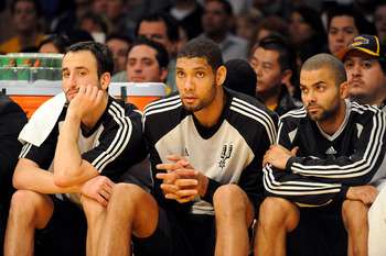 LOS ANGELES, CA - JANUARY 25:  (L-R) Manu Ginobili #20, Tim Duncan #21, and Tony Parker #9 of the San Antonio Spurs watch from the sidelines during the third quarter against the Los Angeles Lakers at the Staples Center on January 25, 2009 in Los Angeles,