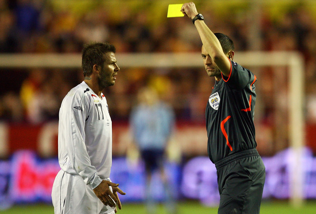 SEVILLE, SPAIN - FEBRUARY 11:  David Beckham of England is shown the yellow card by Stephane Lannoy of France during the International Friendly between Spain and England at the Ramon Sanchez Pizjuan Stadium on February 11, 2009 in Seville, Spain.  (Photo