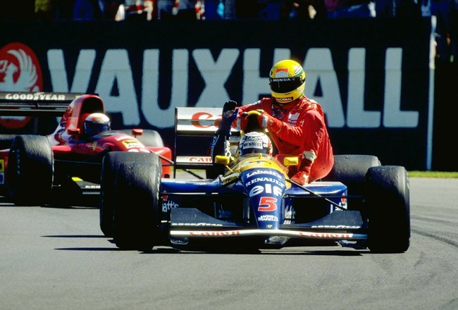 1991:  Williams Renault driver Nigel Mansell of Great Britain gives McLaren Honda driver Ayrton Senna of Brazil a lift home after the British Grand Prix at the Silverstone circuit in England. Mansell finished in first place and Senna retired from the race