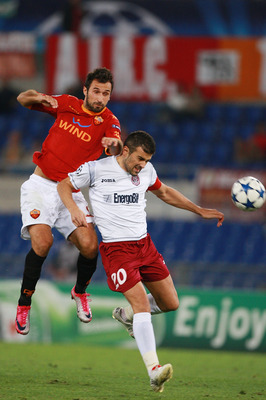 ROME - SEPTEMBER 28:  Mirko Vucinic (UP) of AS Roma competes for the ball with Cadu of CFR Cluj during the UEFA Champions League group E match between AS Roma and CFR Cluj at Stadio Olimpico on September 28, 2010 in Rome, Italy.  (Photo by Paolo Bruno/Get