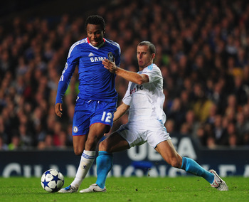LONDON, ENGLAND - SEPTEMBER 28:  John Obi Mikel of Chelsea is challenged by Benoit Cheyrou of Marseille during the UEFA Champions League Group F match between Chelsea and Marseille at Stamford Bridge on September 28, 2010 in London, England.  (Photo by Mi