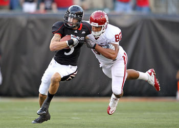 CINCINNATI - SEPTEMBER 25:  D J Woods #3 of the Cincinnati Bearcats runs with the ball while defended by James Hanna #82 of the Oklahoma Sooners at Paul Brown Stadium on September 25, 2010 in Cincinnati, Ohio.  (Photo by Andy Lyons/Getty Images)
