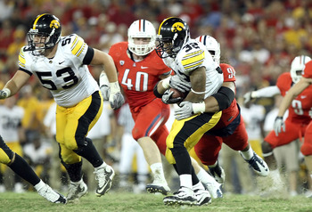 TUCSON, AZ - SEPTEMBER 18:  Runningback Adam Robinson #32 of the Iowa Hawkeyes is tackled for a 2 yard loss by Lolomana Mikaele #94 of the Arizona Wildcats during the college football game at Arizona Stadium on September 18, 2010 in Tucson, Arizona.  The