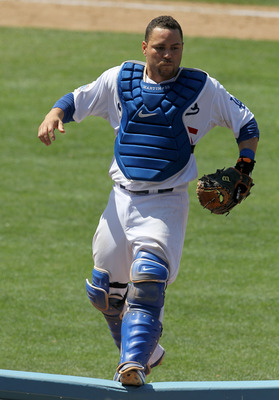 LOS ANGELES, CA - JULY 25:  Catcher Russell Martin #55 of the Los Angeles Dodgers jumps onto a rail beside the New York Mets dugouts as he pursues a pop foul ball that fell into the stands on July 25, 2010 at Dodger Stadium in Los Angeles, California.   T