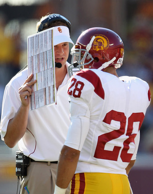 MINNEAPOLIS - SEPTEMBER 18:  Head coach Lane Kiffin of the USC Trojans confers with Dillon Baxter #28 during the game against the Minnesota Golden Gophers on September 18, 2010 at TCF Bank Stadium in Minneapolis, Minnesota.  (Photo by Jamie Squire/Getty I