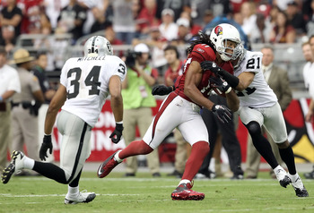 GLENDALE, AZ - SEPTEMBER 26:  Runningback Larry Fitzgerald #11 of the Arizona Cardinals runs with the football after a reception against Nnamdi Asomugha #21 and Mike Mitchell #34 of the Oakland Raiders during the third quarter of the NFL game at the Unive