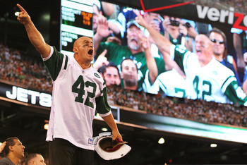 EAST RUTHERFORD, NJ - SEPTEMBER 19:  New York Jets fan Fireman Ed Anzalone leads the crowd in a cheer against the New England Patriots during their  game on September 19, 2010 at the New Meadowlands Stadium  in East Rutherford, New Jersey.  (Photo by Al B