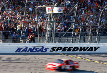 KANSAS CITY, KS - OCTOBER 04:  Tony Stewart, driver of the #14 Office Depot/Old Spice Chevrolet, crosses the start/finish line to take the checkered flag and win the NASCAR Sprint Cup Series Price Chopper 400 presented by Kraft Foods at the Kansas Speedwa