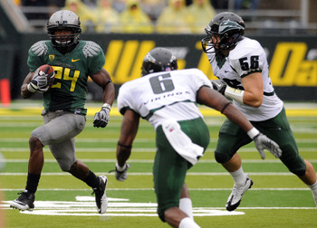 EUGENE, OR - SEPTEMBER 18: Running back Kenjon Barner #24 of the Oregon Ducks turns the corner as cornerback David Ross and linebacker Ryan Rau #56 of the Portland State Vikings close in during the first quarter of the game against the Portland State Viki