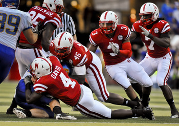LINCOLN, NEBRASKA - SEPTEMBER 25: Nebraska Cornhuskers linebacker Lavonte David #4, linebacker Eric Martin #46, safety Rickey Thenarse #3, defensive back DeJon Gomes #7 bring down South Dakota State Jackrabbits running back Kyle Minett #30 during first ha