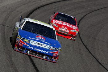 KANSAS CITY, KS - OCTOBER 04:  Greg Biffle, driver of the #M / Sherwin Williams Ford, leads Tony Stewart, driver of the #14 Office Depot / Old Spice Chevrolet, during the NASCAR Sprint Cup Series Price Chopper 400 presented by Kraft Foods at the Kansas Sp