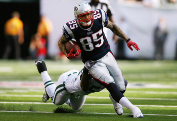 EAST RUTHERFORD, NJ - SEPTEMBER 19:  Aaron Hernandez #85 of the New England Patriots runs through a tackle from David Harris #52 of the New York Jets during the first quarter at the New Meadowlands Stadium on September 19, 2010 in East Rutherford, New Jer