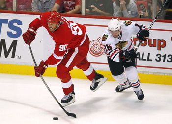 DETROIT - SEPTEMBER 24:  Mike Modano #90 of the Detroit Red Wings passes away from Ryan Potulny #16 of the Chicago Blackhawks during a pre season game on September 24, 2010 at Joe Louis Arena in Detroit, Michigan.  (Photo by Gregory Shamus/Getty Images)