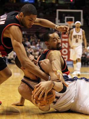 EAST RUTHERFORD, NJ - FEBRUARY 23:  Brook Lopez #11 of the New Jersey Nets fights for a loose ball against Juwan Howard #6 and Nicolas Batum #88 of the Portland Trail Blazers at the Izod Center on February 23, 2010 in East Rutherford, New Jersey.The Blaze