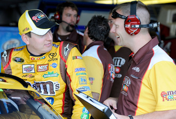 WATKINS GLEN, NY - AUGUST 06:  Kyle Busch (L), driver of the #18 M&M's Toyota, talks with his crew chief Dave Rogers in the garage during practice for the NASCAR Heluva Good! Sour Cream Dips at The Glen on August 6, 2010 in Watkins Glen, New York.  (Photo