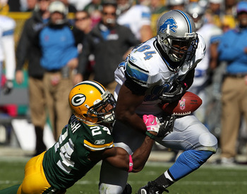 GREEN BAY, WI - OCTOBER 03: Brandon Pettigrew #84 of the Detroit Lions drops a pass as he is hit by Jarrett Bush #24 of the Green Bay Packers at Lambeau Field on October 3, 2010 in Green Bay, Wisconsin. The Packers defeated the Lions 28-26.  (Photo by Jon
