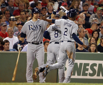 BOSTON - SEPTEMBER 07:  Jason Bartlett #8 and B.J. Upton #2 of the Tampa Bay Rays are congratulated by Ben Zobrist #18 after Bartlett  hit a two run homer in the fifth inning against the Boston Red Sox on September 7, 2010 at Fenway Park in Boston, Massac