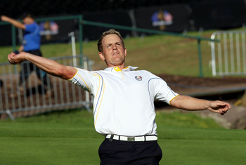 NEWPORT, WALES - OCTOBER 04:  Luke Donald of Europe throws his ball to the crowd after he won his match on the 18th green in the singles matches during the 2010 Ryder Cup at the Celtic Manor Resort on October 4, 2010 in Newport, Wales.  (Photo by Ross Kin