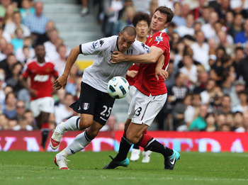 LONDON, ENGLAND - AUGUST 22:  Jonny Evans of Manchester United battles with Bobby Zamora of Fulham during the Barclays Premier League match between Fulham and Manchester United at Craven Cottage on August 22, 2010 in London, England.  (Photo by Phil Cole/