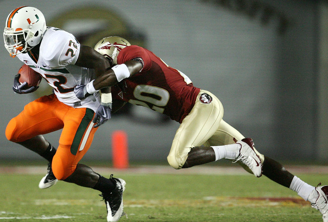 TALLAHASSEE, FL - SEPTEMBER 07: Running back Mike James #22 of the Miami Hurricanes tries to avoid being brought down by safety Jamie Robinson #20 of the Florida State Seminoles at Doak Campbell Stadium on September 7, 2009 in Tallahassee, Florida. Miami