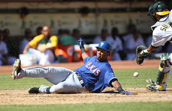 OAKLAND, CA - SEPTEMBER 26:  Kurt Suzuki #8 of the Oakland Athletics fails to tag out Julio Borbon #29 of the Texas Rangers on a single by David Murphy in the second inning during a Major League Baseball game at the Oakland-Alameda County Coliseum on Sept