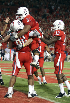 TUCSON, AZ - SEPTEMBER 25:  Jovon Hayes #57 of the Arizona Wildcats jumps into the arms of wide receiver Juron Criner #82 after Criner caught the game winning 3 yard touchdown reception against the California Golden Bears during the fourth quarter of the