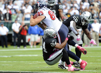 OAKLAND, CA - OCTOBER 3: Tighe End Joel Dreesen #85 of the Houston Texans runs over Michael Huff #24 of the Oakland Raiders into the endzone for a touchdown during an NFL football game October 3, 2010 at The Oakland-Alameda County Coliseum in Oakland, Cal