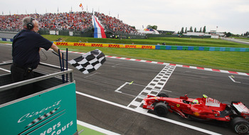 NEVERS, FRANCE - JUNE 22:  Felipe Massa of Brazil and Ferrari crosses the finish line to win the French Formula One Grand Prix at the Circuit de Nevers Magny-Cours on June 22, 2008 in Nevers, France.  (Photo by Mark Thompson/Getty Images)