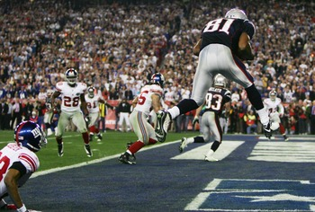 GLENDALE, AZ - FEBRUARY 03:  Wide receiver Randy Moss #81 of the New England Patriots catches a six-yard touchdown pass from Tom Brady #12 in front of cornerback Corey Webster #23 of the New York Giants in the fourth quarter of Super Bowl XLII on February